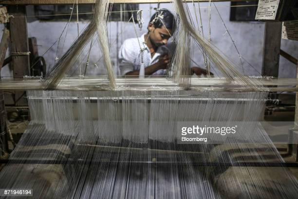 A weaver uses a handloom to make a silk saree in a workshop in Varanasi Uttar Pradesh India on Friday Oct 27 2017 In Varanasi where the manufacture...