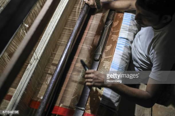 A weaver uses a shuttle on a handloom to make a silk saree in a workshop in Varanasi Uttar Pradesh India on Friday Oct 27 2017 In Varanasi where the...