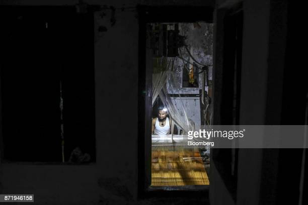 A weaver using a handloom to make a silk saree is seen through the window of a workshop at night in Varanasi Uttar Pradesh India on Saturday Oct 28...