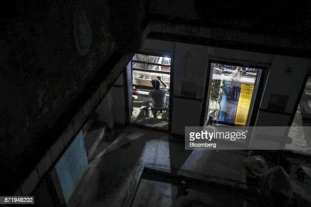 A weaver using a handloom to make a silk saree is seen through the window of a workshop at night in Varanasi Uttar Pradesh India on Friday Oct 27...