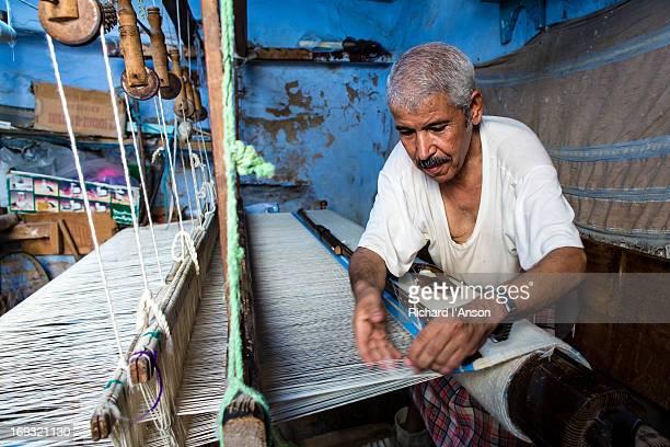 Weaver working on loom in workshop in Medina