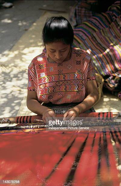 A weaver working with red textiles on a backstrap loom Guatemala