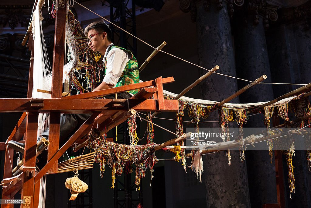 A weaver works on an old handloom during the Laurence Xu show as part of Paris Fashion Week Haute-Couture Fall/Winter 2013-2014 at Pavillon Cambon on July 4, 2013 in Paris, France.