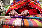 A close up of a woman weaving in Peru with bright traditional clothes.
