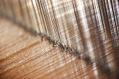 Close-up of the cotton yarn which is being woven by a loom