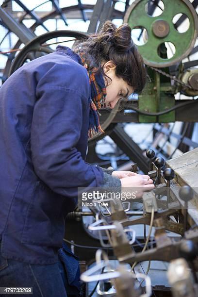 weaving technician loading cone winding machine.