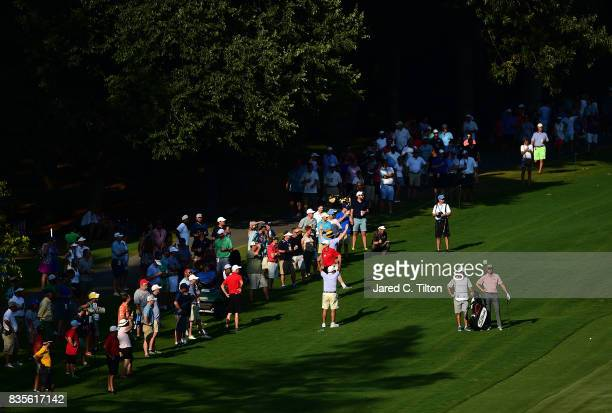 Webb Simpson and his caddie look on from the rough on the 18th hole during the third round of the Wyndham Championship at Sedgefield Country Club on...