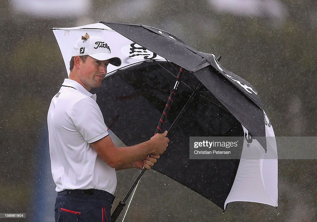 Webb Simpson shields himself from the wind and rain under an umbrella on the second hole green during the first round of the Hyundai Tournament of Champions at the Plantation Course on January 4, 2013 in Kapalua, Hawaii.