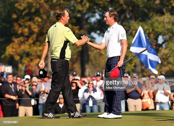 Webb Simpsonof the United States is congratulated by Peter Hanson on the 14th green after defeating the Lawrie/Hanson team 54 during the Afternoon...