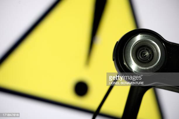 A webcam is positioned in front of a danger sign on June 28 2013 in Paris A new type of crook hunts its victims on the web pushing them to erotic...