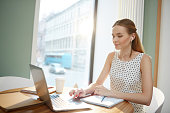 Pretty young businesswoman in elegant blouse listening and watching webcast while sitting by desk in front of laptop