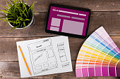 website wireframe sketch and digital tablet on brown wooden table with color samples