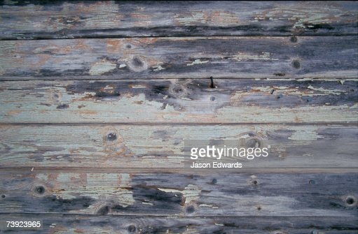 Paint peeling off the planks of an old country house.