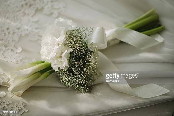 Wedding bouquet laying on white gown