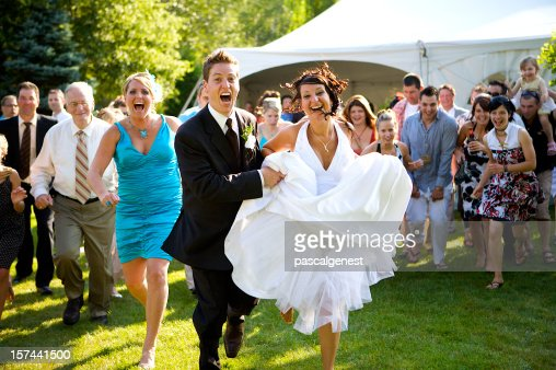 wedding bride and groom running with the crowd