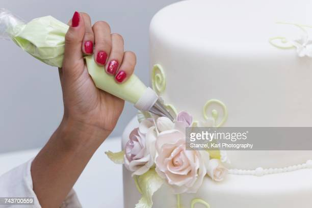 A wedding cake being decorated