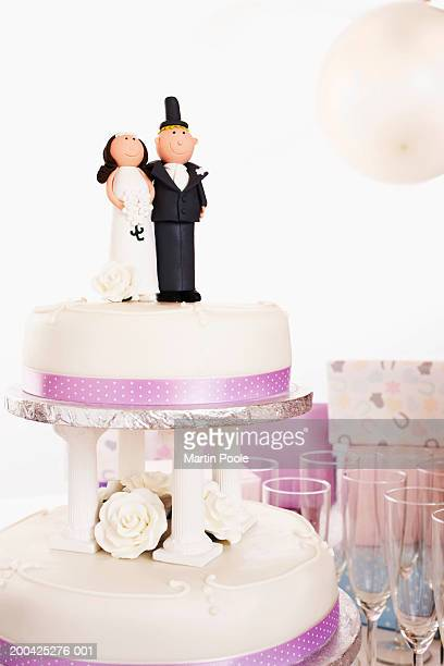 Wedding cake decorated with bride and groom figures on table by gifts