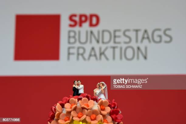 A wedding cake in rainbow colors and decorated with figurines of two women and two men is pictured at the offices of the social democratic SPD's...