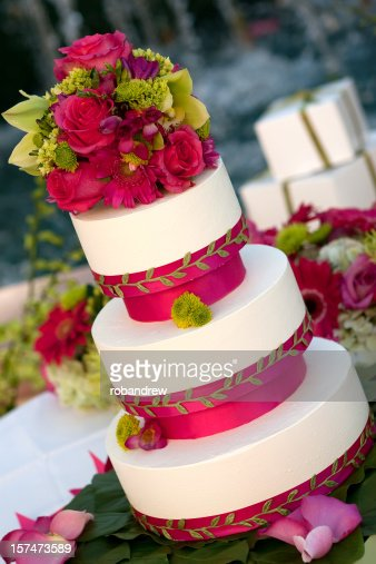 Wedding cake in white and pink with flowers on top