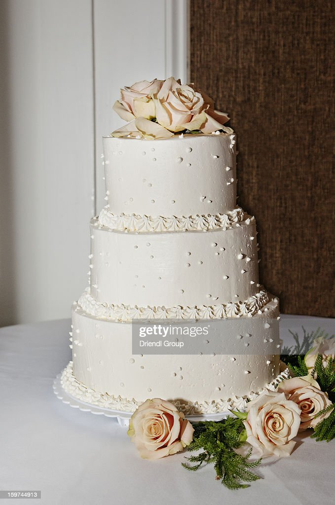 A wedding cake trimed in peach roses. : Stock Photo