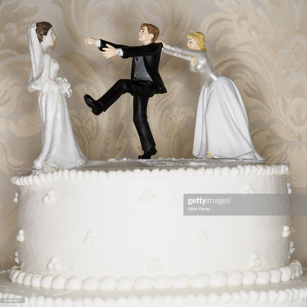 Wedding cake visual metaphor with figurine cake toppers : Stock Photo