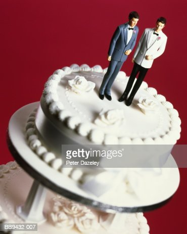 Wedding cake with two groom decorations, pink background