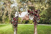 Wedding ceremony in rustic style decorated with different red flowers, white textile and chairs in forest