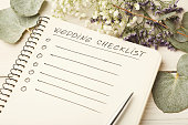 Wedding checklist with copy space and cute flowers on the white desktop. Marriage planner concept, copy space.