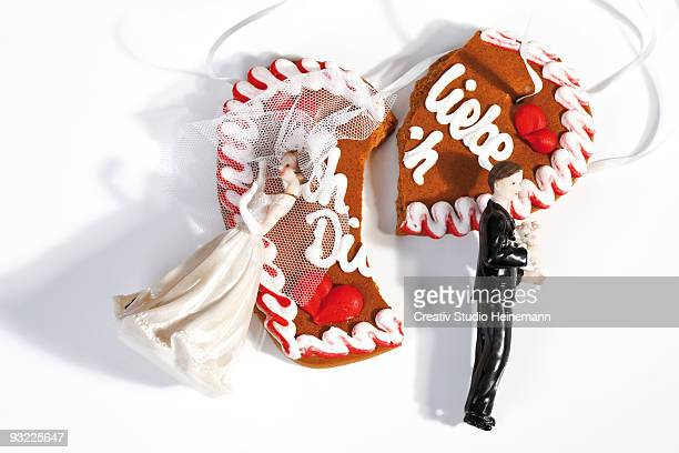 Wedding couple figurines and broken gingerbread heart on white background, close-up