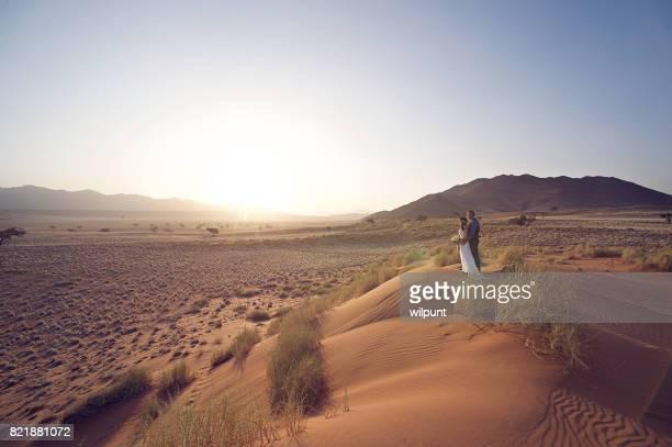 Bruidspaar op zand duin bij zonsondergang