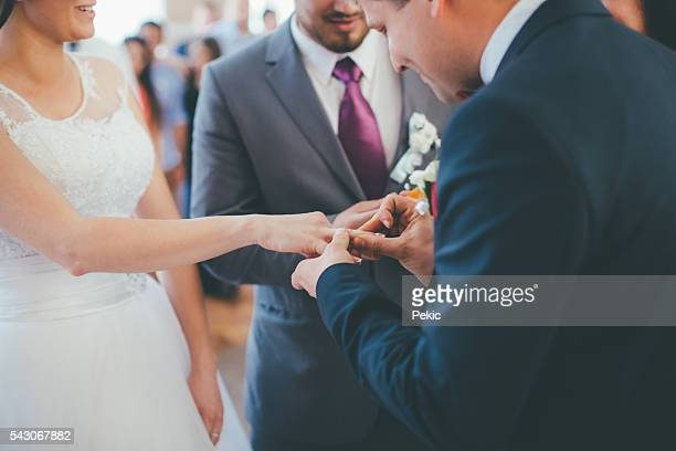 Wedding couple on their ceremony changing their wedding rings
