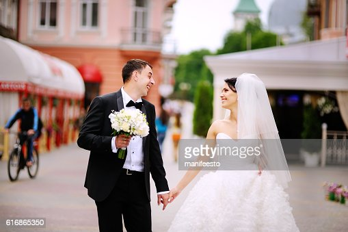 Wedding couple walking street, groom and bride holding hands : Stock Photo