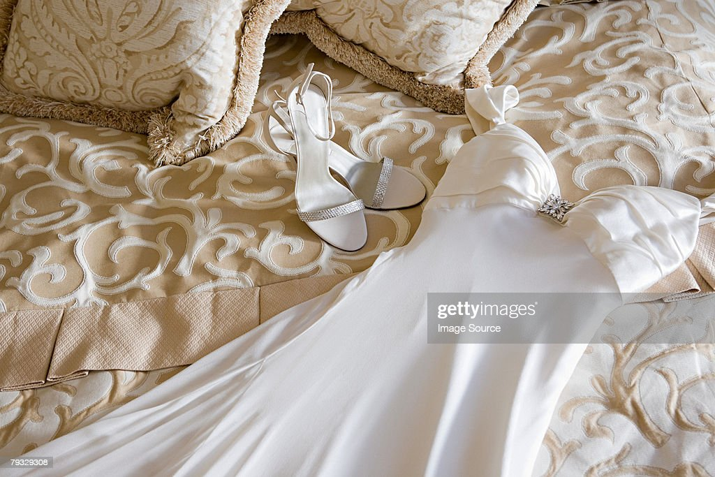 wedding dress and shoes on bed stock photo
