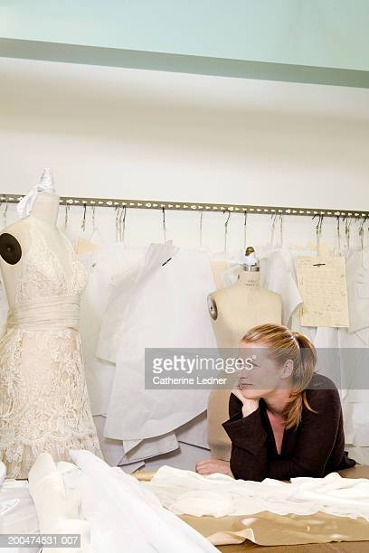 Wedding dress designer in workshop surrounded by patterns