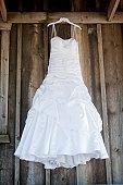 Wedding dress hanging against old wood