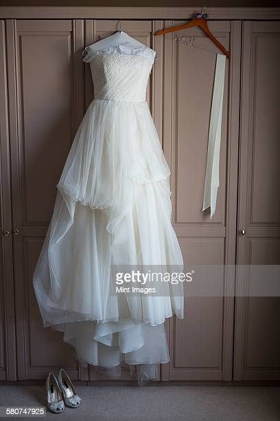 Wedding dress hanging on a wardrobe door, wedding shoes on the floor.
