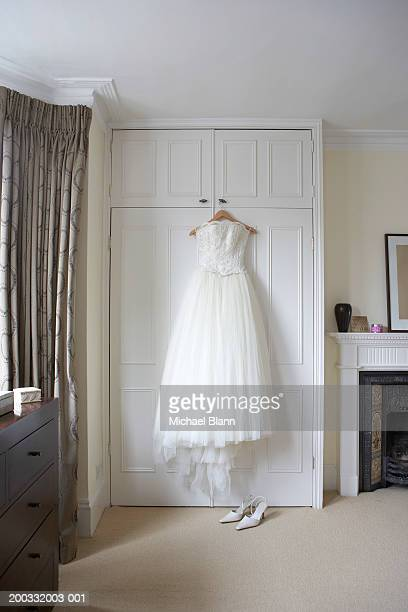 Wedding dress hanging on wardrobe doors, white shoes on floor