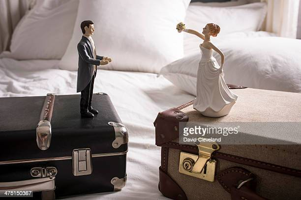 Wedding figurines on separate suitcases