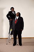 very big and tall groomsman and groom next to each other at wedding and groom on ladder