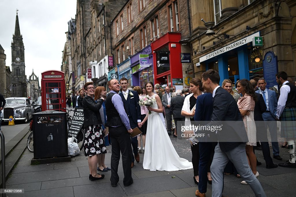 Wedding guests congregate on the pavement of the Royal Mile near to the Scottish Parliament building, in Edinburgh, Scotland on June 25, 2016. Scotland wants immediate talks with the European Union on protecting its place in the bloc, after Britain's vote to leave the EU, First Minister Nicola Sturgeon said Saturday. Speaking after an emergency meeting of her cabinet, Sturgeon said it had agreed to seek 'immediate discussions with the EU institutions and other EU member states to explore all possible options to protect Scotland's place in the EU.' SCARFF