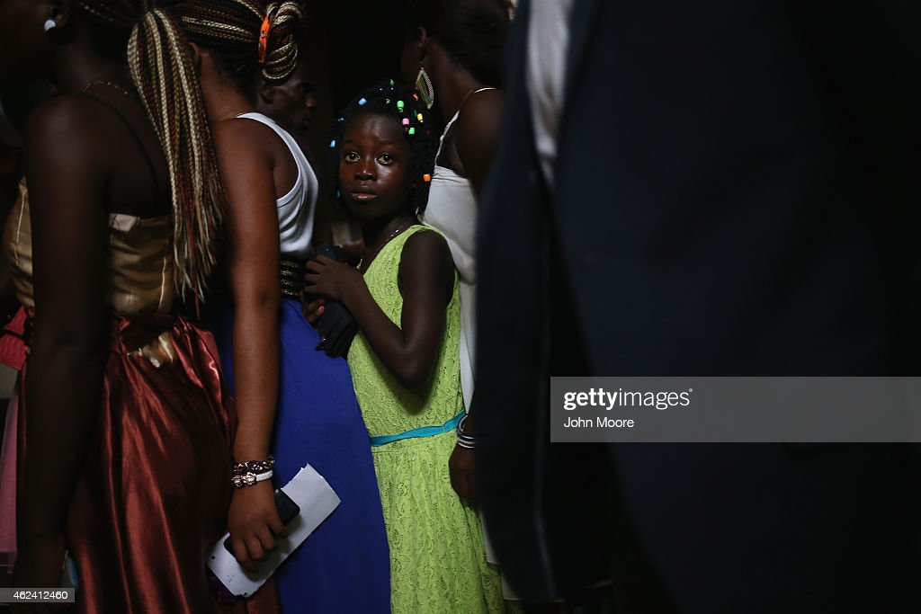 Wedding guests stand close in line while waiting to eat at the reception on January 24 2015 in Monrovia Liberia The bride and groom had waited until...