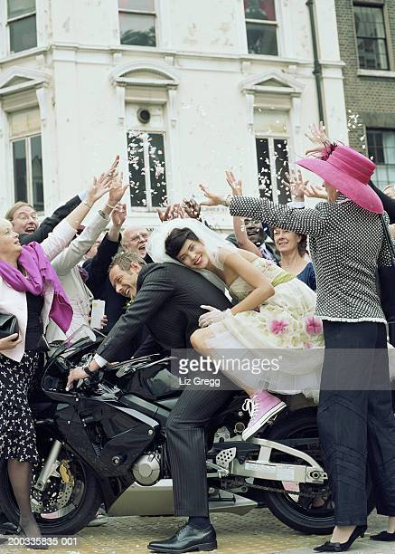 Wedding guests throwing confetti over bride and groom on motorbike
