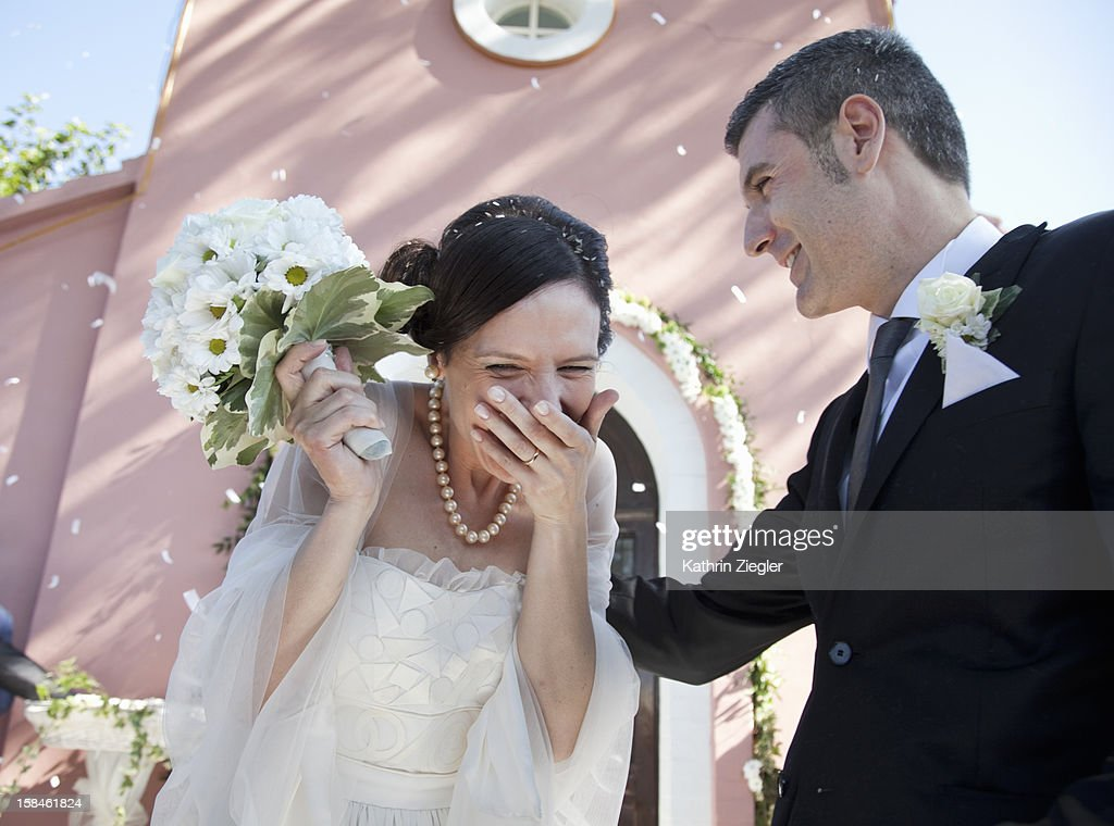 wedding guests throwing rice at bride and groom : Stock Photo