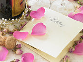 Wedding Invitation Next To Champagne Bottle Surrounded By Flower Petals