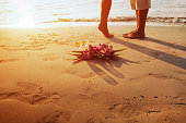 wedding on the beach, feet of romantic couple and two glasses of champagne at sunset