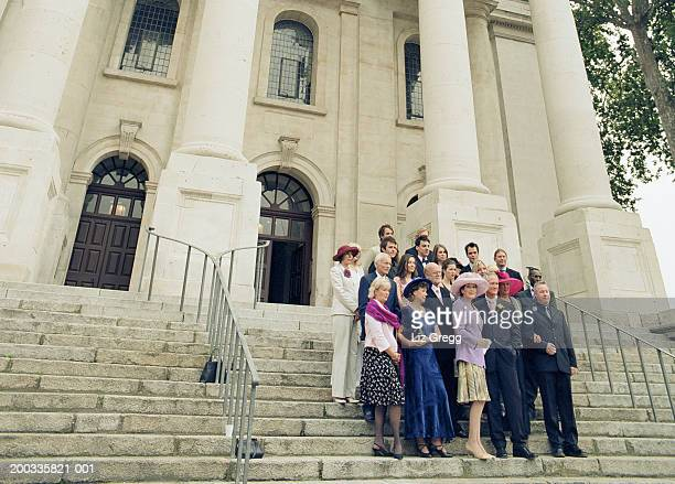 Wedding party standing on church steps waving