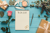 Wedding to do list, top view. Present box, calendar for marriage planning, rings and various bridal stuff on blue rustic table. Memmorable date organization background, copy space