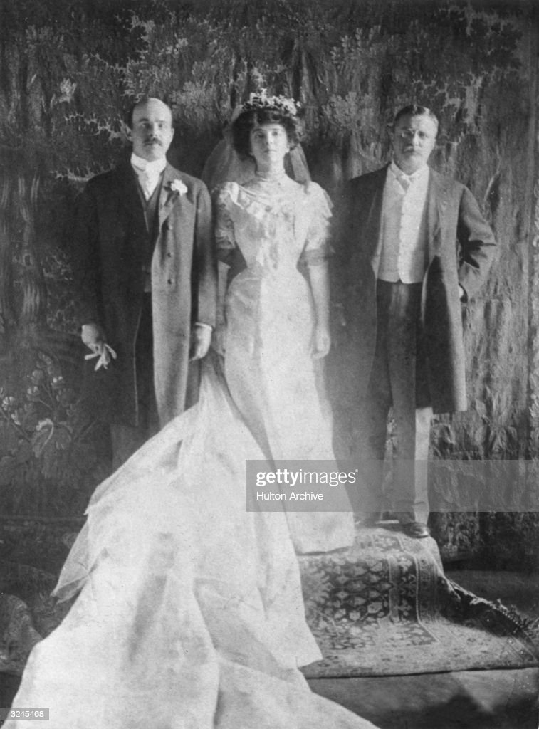 Wedding portrait of Nicholas Longworth (left) and Alice Roosevelt posing with the bride's father, U.S. president Theodore Roosevelt. The bride is wearing a white dress, white gloves, a veil, and a train.
