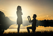 Wedding proposal concept. Young couple have dating at sun set. Man in love is kneeling on knees and giving wedding ring to surprised woman.