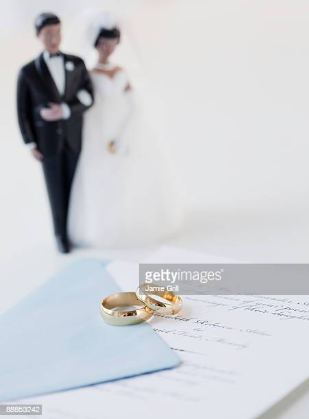 Wedding rings by bride and groom cake toppers on marriage certificate